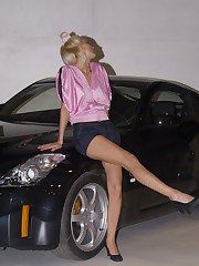Blonde in pink top and black shorts shot near the car