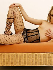 Sexy doll in fishnet pantyhose poses with dildo